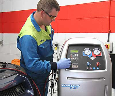 a mechanic performing a full high pressure air conditioning system clean on a volvo