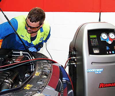 air conditioning expert repairing and regassing a car air con system