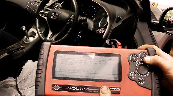 close up of computer fault finding diagnosis equipment with screen showing the device connecting to the vehicles on board computer to diagnose any faults