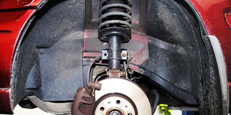 close up underneath a vauxhall showing leaking shock absorbers