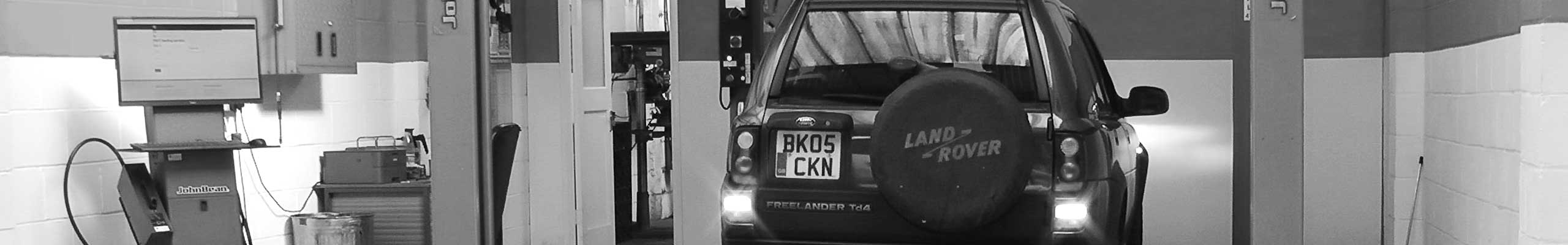 very classy black and white expert image of excels mot testing bay with a land rover part way through testing