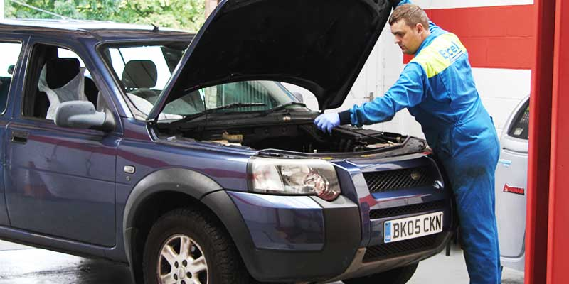 mechanic checking a land rover cars electrical systems with bonnet up for its annual mot test