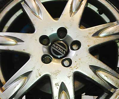 a very diry old volvo wheel close up
