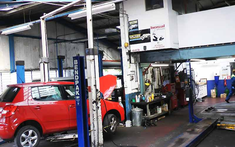 excel automotives repair garage inside with cars on ramps and mechanics working