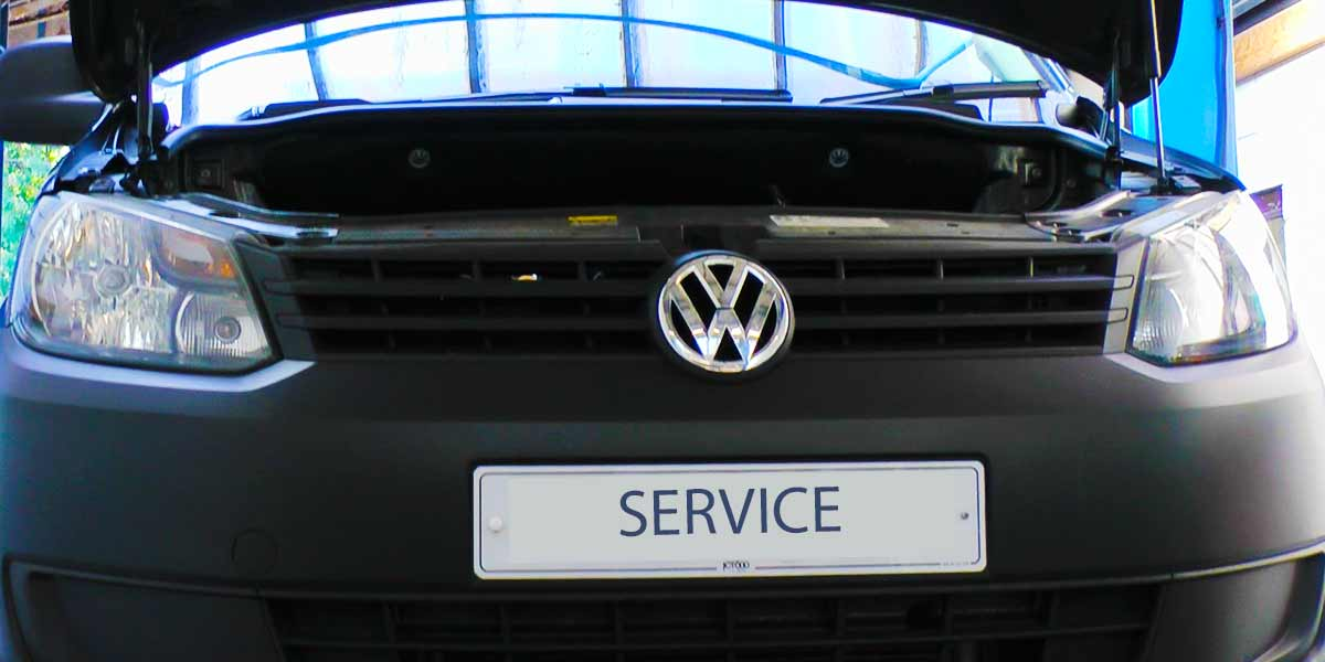 close up of a volkswagon car with bonnet up getting an annual vehicle service