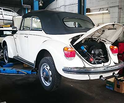 a volkswagon beetle in need of engine repairs with its boot lid up revealing a very poorly engine