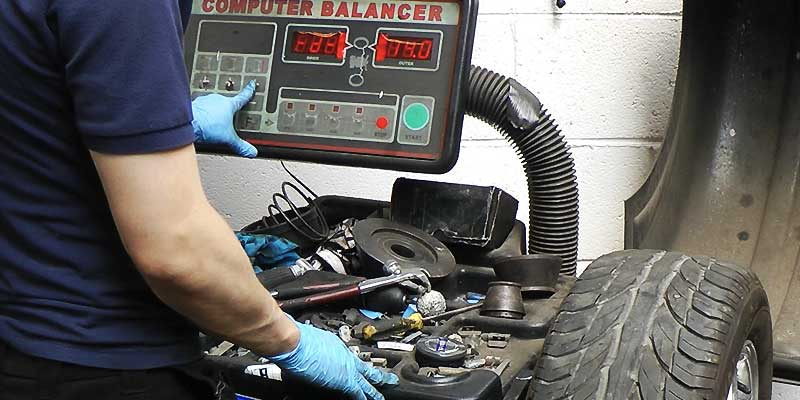 a mechanic balancing a car wheel on excels specialist wheel balancing machine